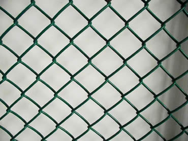 A piece of green color chain link helideck mesh on the ground.