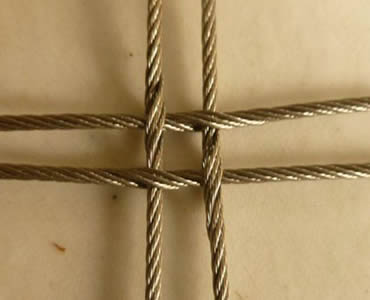 A piece of cross-shaped stainless steel square rope mesh is on the floor.