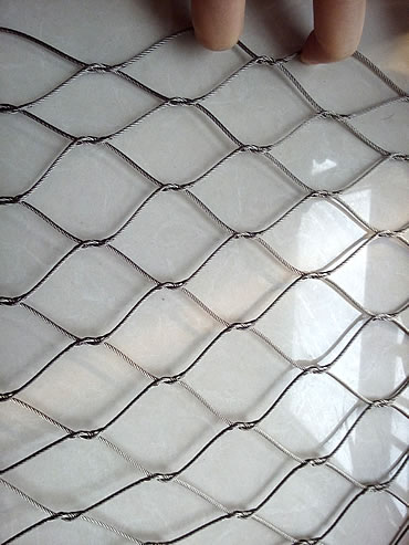A piece of knotted rope mesh with diamond holes.