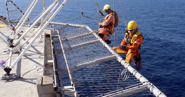Two workers are installing the stainless steel ferrule helideck rope mesh.