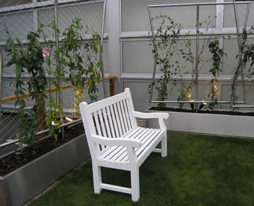 Stainless steel ferrule rope mesh is installed in the yard with a white chair in it.