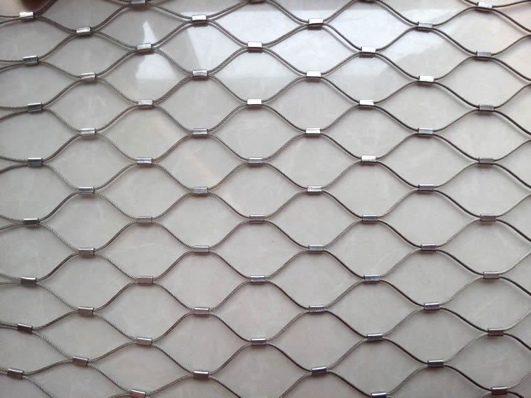 A piece of galvanized ferrule rope mesh with uniform mesh holes.
