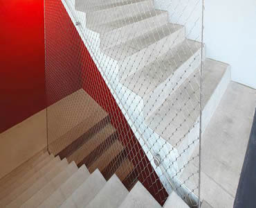 Stainless steel ferrule rope mesh is installed as the wall beside the stair.