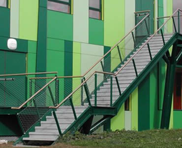 Stainless steel ferrule rope mesh is installed as the balustrade of outdoor green stair.