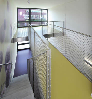 Stainless steel ferrule rope mesh is installed as the balustrade infill of concrete stair and yellow passage.