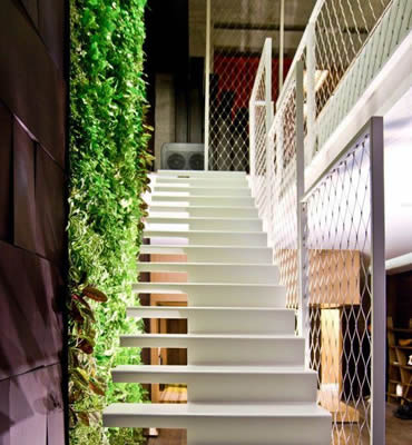 Stainless steel ferrule rope mesh is installed as balustrade infill of white stairs with green plants beside it.
