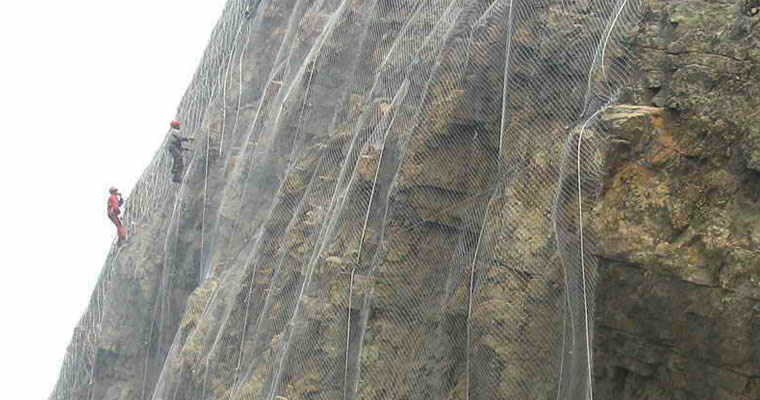 Several workers are installing the slope protection rope mesh.