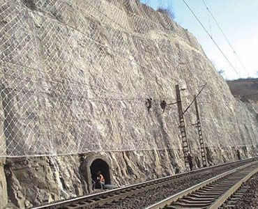 A large piece of slope protection rope mesh is covered on slope beside railway.