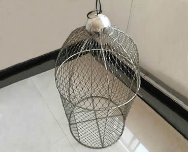 A bird cage made up of stainless steel ferrule rope mesh is on the floor.